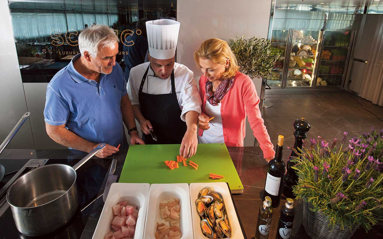 couple preparing food with chef